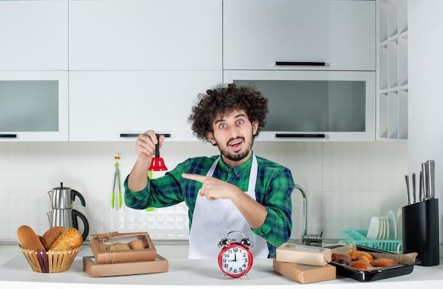 Vista frontal del joven confiado de pie detrás de la mesa varios pasteles y sosteniendo la campana de anillo rojo en la cocina blanca