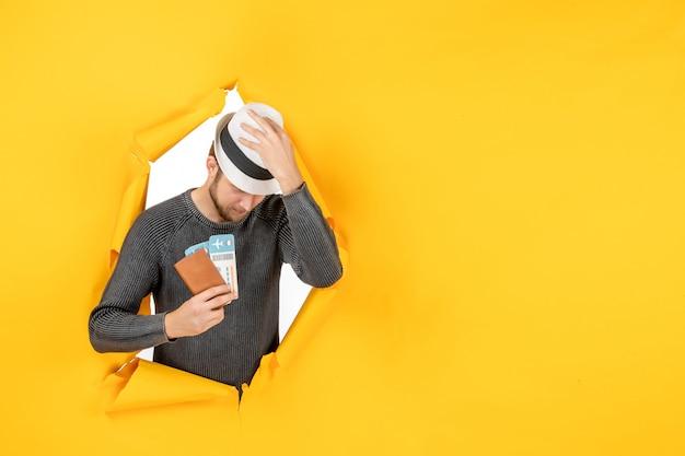 Vista frontal del joven confiado con sombrero y sosteniendo pasaporte extranjero con boleto en un rasgado en la pared amarilla