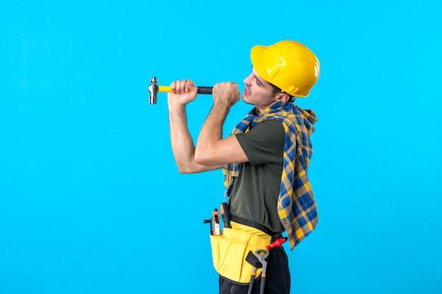 Vista frontal joven constructor masculino sosteniendo un martillo sobre el fondo azul trabajador edificio arquitectura constructor trabajo plano