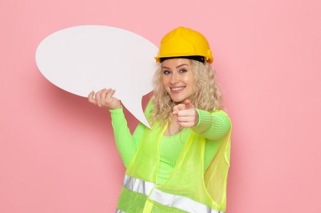 Vista frontal joven constructora en traje de construcción verde casco amarillo con cartel blanco con sonrisa en el trabajo de construcción de arquitectura de trabajo de espacio rosa