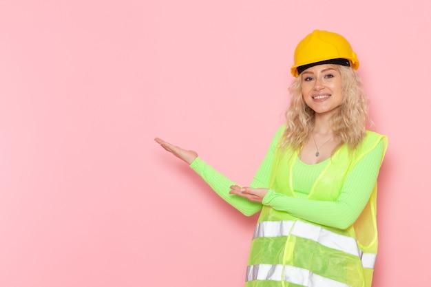 Vista frontal joven constructora en traje de construcción verde casco amarillo sonriendo y dando la bienvenida a la construcción de arquitectura de trabajo de espacio rosa