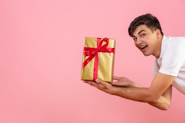 Vista frontal del joven dando regalo de navidad a alguien en la pared rosa