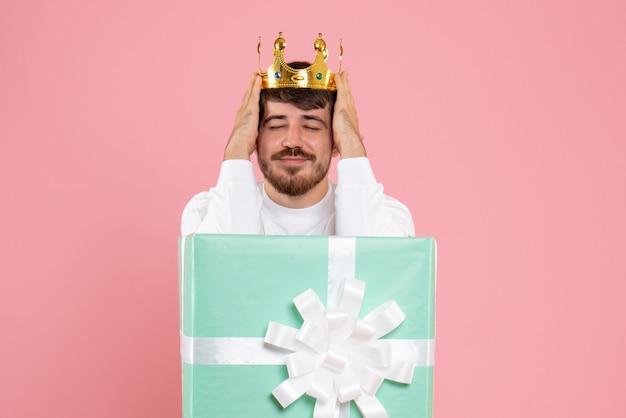 Vista frontal del joven dentro del cuadro actual con corona en la pared rosa
