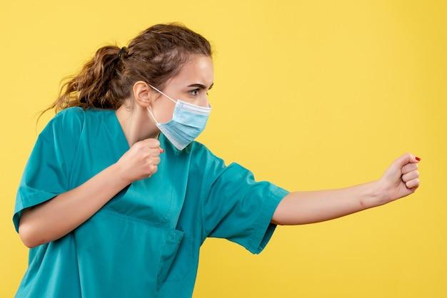 Vista frontal de la joven doctora en camisa médica y máscara estéril en la pared amarilla