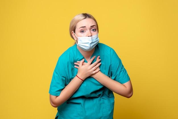 Vista frontal de la joven doctora en camisa médica y máscara en la pared amarilla