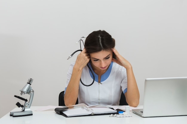Vista frontal joven doctora pensando Foto gratis