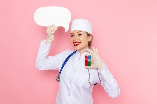 Vista frontal joven doctora en traje médico blanco con estetoscopio azul sosteniendo frascos y cartel blanco sonriendo en la salud del hospital médico de medicina espacial rosa