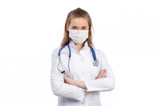 Una vista frontal joven doctora en traje médico blanco con estetoscopio con máscara protectora blanca sobre el blanco