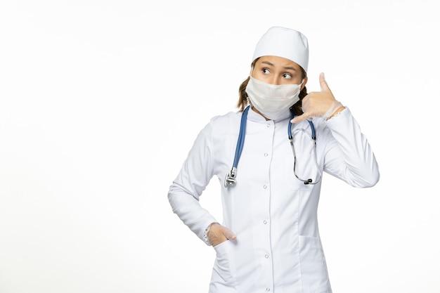 Vista frontal joven doctora en traje médico blanco y con máscara estéril debido al coronavirus en la superficie blanca clara
