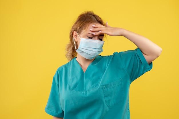 Vista frontal de la joven doctora en traje médico y máscara con dolor de cabeza en la pared amarilla