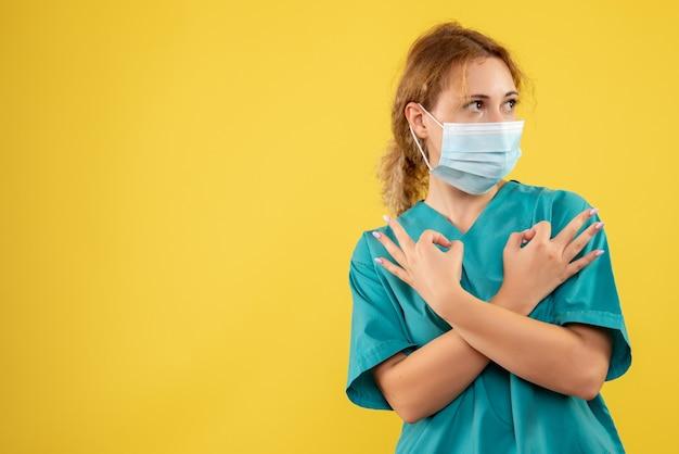 Vista frontal de la joven doctora en traje médico y máscara en la pared amarilla