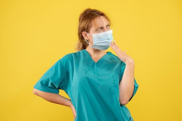 Vista frontal de la joven doctora en traje médico y máscara pensando en la pared amarilla