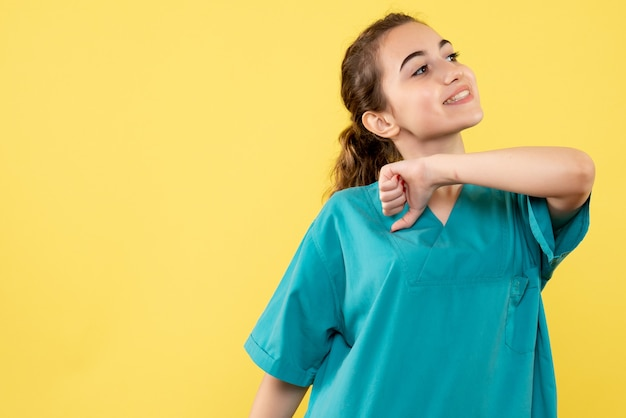Vista frontal joven doctora en traje médico sobre fondo amarillo