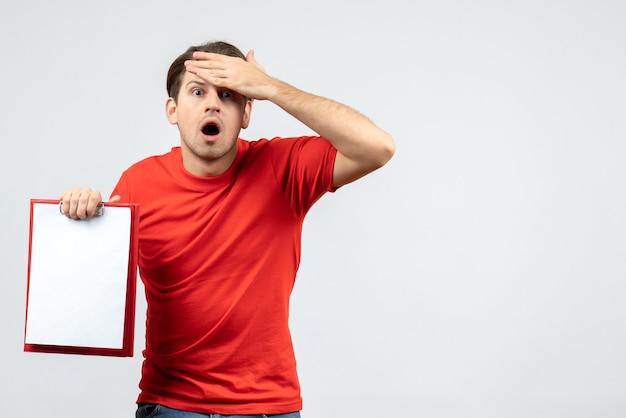 Vista frontal del joven emocional agotado en blusa roja con documento sobre fondo blanco.