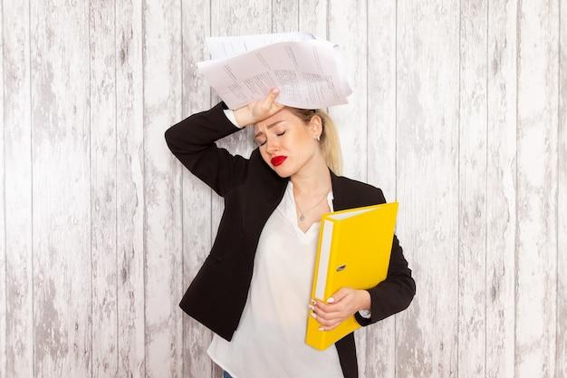 Vista frontal joven empresaria en ropa estricta chaqueta negra con archivos y documentos sobre superficie blanca