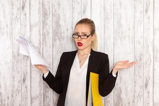 Vista frontal joven empresaria en ropa estricta chaqueta negra leyendo documento sobre superficie blanca