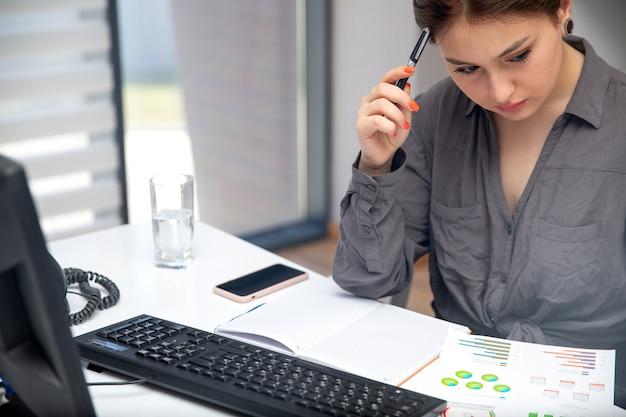 Una vista frontal joven empresaria trabajando en su pc en la mesa junto con teléfono y gráficos escribiendo notas pensando en tecnología de actividades laborales