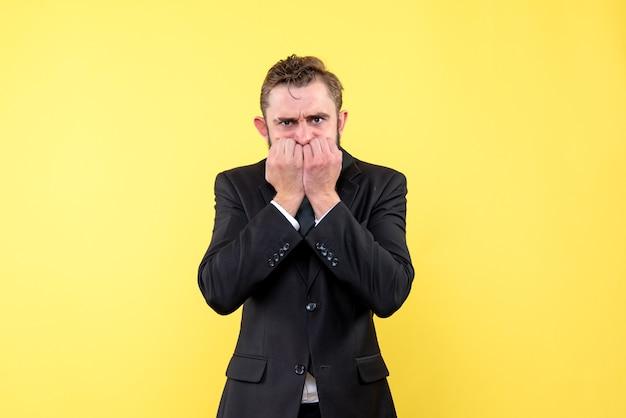 Vista frontal del joven empresario alarmado y toca su rostro con las manos en amarillo