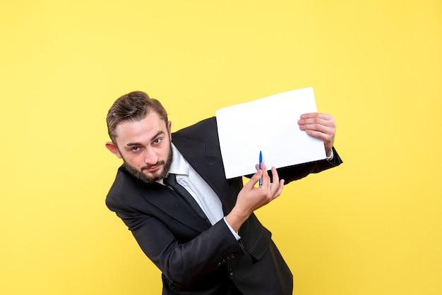 Vista frontal del joven empresario joven apuntando con un bolígrafo a un papel en blanco a un lado a la izquierda en amarillo