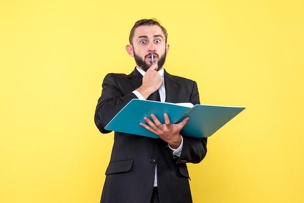 Vista frontal del joven empresario sorprendido tocando la pluma en la boca tiene carpeta azul sobre amarillo