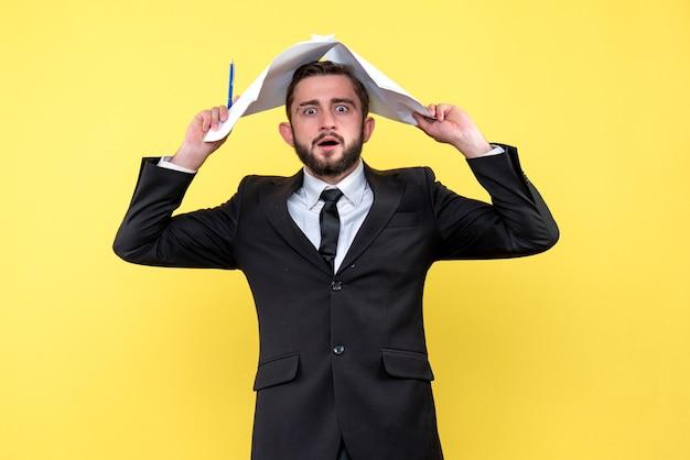 Vista frontal del joven empresario volviéndose loco tocando la cabeza con hojas de papel en blanco sobre amarillo