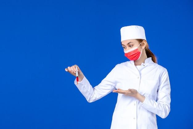 Vista frontal joven enfermera en traje médico blanco con máscara roja e inyección en sus manos en la pared azul