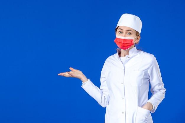 Vista frontal joven enfermera en traje médico con máscara protectora roja en la pared azul