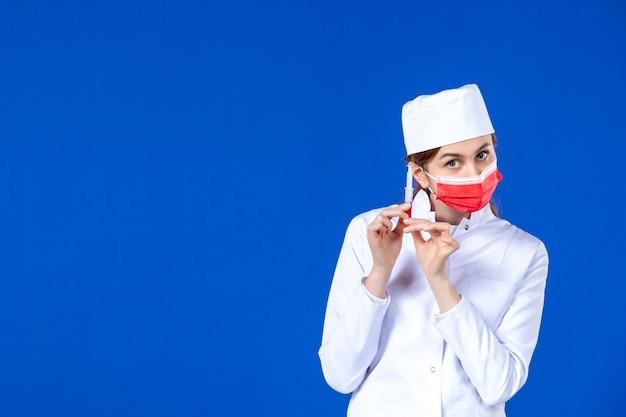 Vista frontal joven enfermera en traje médico con máscara roja e inyección en sus manos en la pared azul