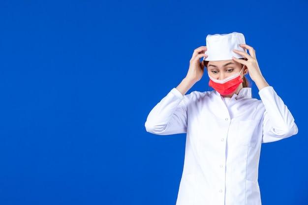 Vista frontal de la joven enfermera en traje médico con máscara roja sobre azul