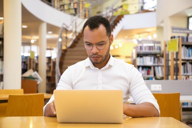 Vista frontal del joven enfocado escribiendo en la computadora portátil en la biblioteca