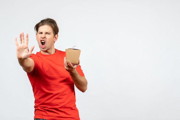 Vista frontal del joven enojado en blusa roja sosteniendo una pequeña caja y mostrando cinco sobre fondo blanco.