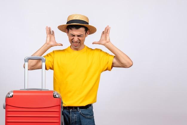 Vista frontal joven enojado con camiseta amarilla y maleta roja