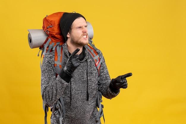 Vista frontal del joven enojado con guantes de cuero y mochila