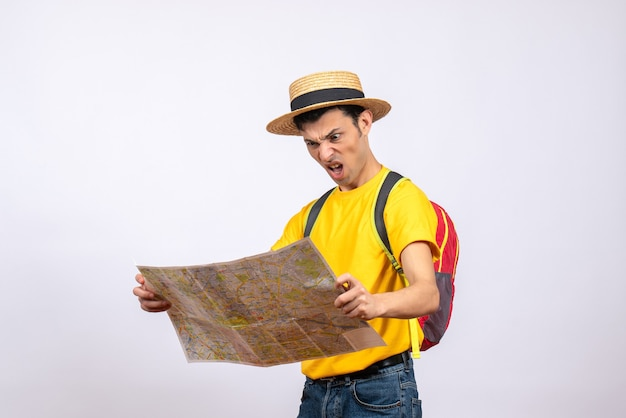 Vista frontal joven enojado con mochila roja y camiseta amarilla mirando el mapa