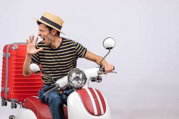 Vista frontal joven enojado con sombrero de paja en ciclomotor gritando