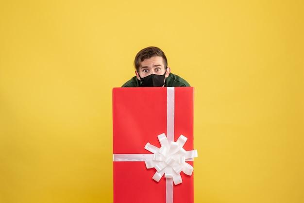 Vista frontal joven escondido detrás de caja de regalo grande en amarillo
