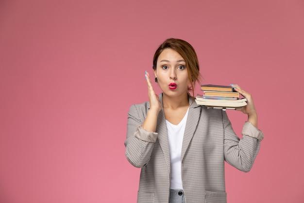 Vista frontal joven estudiante en abrigo gris posando sosteniendo libros con expresión de sorpresa en el estudio de la universidad de lecciones de fondo rosa
