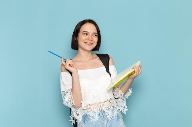 Vista frontal joven estudiante en camisa blanca, jeans y bolso negro escribiendo notas en la escuela universitaria de estudiante de espacio azul