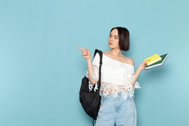 Vista frontal joven estudiante en camisa blanca, jeans y bolso negro sosteniendo cuadernos en el estudiante del espacio azul