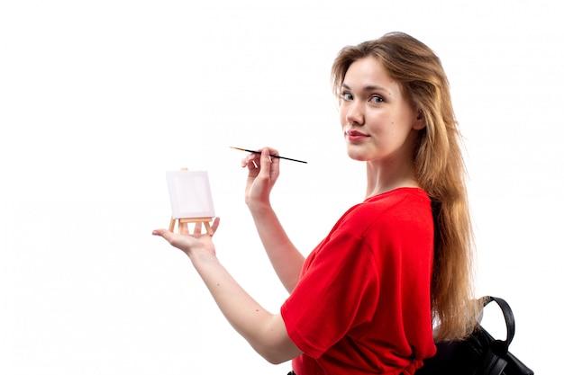 Una vista frontal joven estudiante en camisa roja bolsa negra sosteniendo pincel pintura sonriendo en el blanco