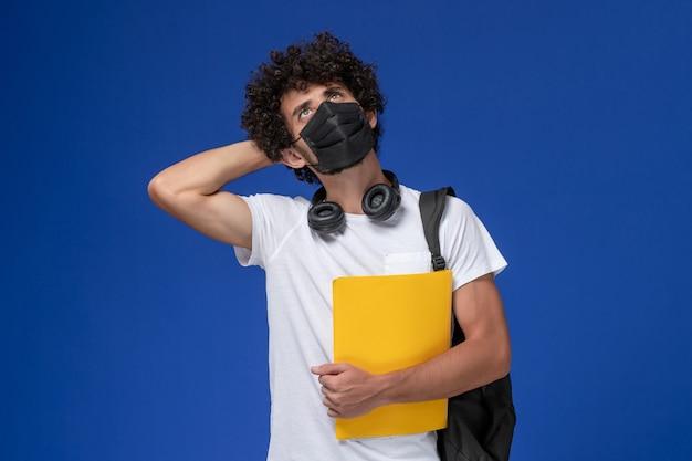 Vista frontal joven estudiante en camiseta blanca con máscara negra y sosteniendo archivos amarillos pensando en fondo azul claro.