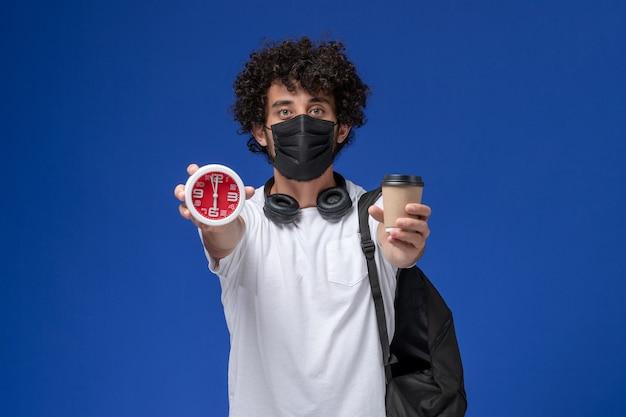 Vista frontal joven estudiante en camiseta blanca con máscara negra y sosteniendo la taza de café con reloj sobre fondo azul claro.