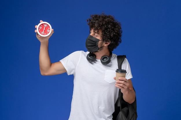 Vista frontal joven estudiante en camiseta blanca con máscara negra y sosteniendo la taza de café con reloj sobre fondo azul.
