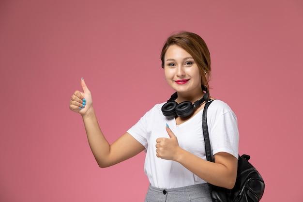 Vista frontal joven estudiante en camiseta blanca y pantalón gris con auriculares y sonrisa sobre fondo rosa lecciones estudiantiles universidad universitaria