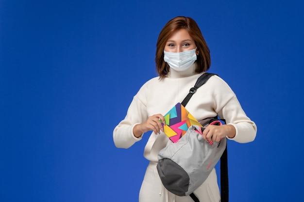 Vista frontal joven estudiante en jersey blanco con máscara y bolsa sosteniendo cuaderno en la pared azul