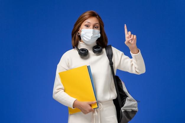 Vista frontal joven estudiante en jersey blanco con máscara y mochila sosteniendo archivos en la pared azul