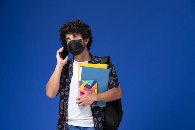 Vista frontal joven estudiante con máscara negra con mochila sosteniendo archivos y hablando por teléfono sobre fondo azul.