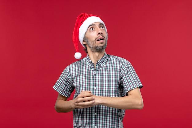 Vista frontal joven con expresión confusa en la pared roja masculina vacaciones de año nuevo rojo