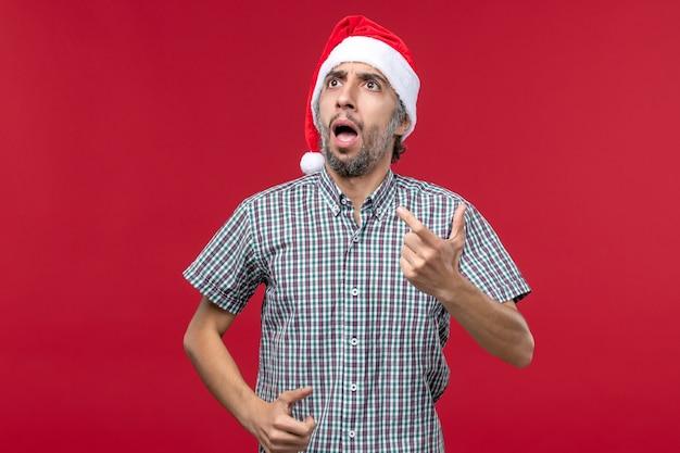 Vista frontal joven con expresión confusa en la pared roja vacaciones año nuevo rojo