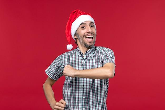 Vista frontal joven con expresión emocionada en la pared roja masculina de vacaciones de año nuevo rojo